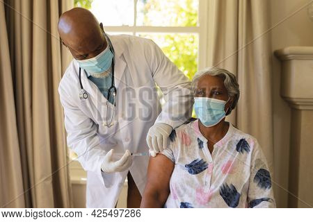 Senior african american woman and male doctor in face masks, woman receiving vaccination. retirement and senior lifestyle during covid 19 pandemic concept.