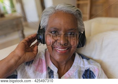 Portrait of senior african american woman sitting on sofa wearing headphones smiling. retreat, retirement and happy senior lifestyle concept.