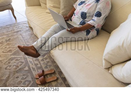 Senior african american woman sitting on sofa using laptop. retreat, retirement and happy senior lifestyle concept.