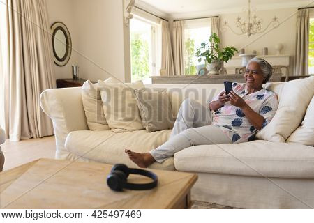 Senior african american woman sitting on sofa using smartphone and smiling. retreat, retirement and happy senior lifestyle concept.