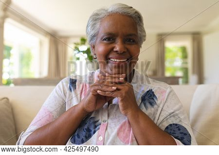 Portrait of senior african american woman sitting on sofa looking at camera and smiling. retreat, retirement and happy senior lifestyle concept.