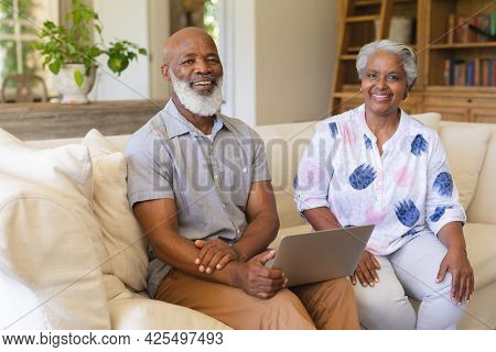 Portrait of senior african american couple sitting on sofa looking at camera and smiling. retreat, retirement and happy senior lifestyle concept.