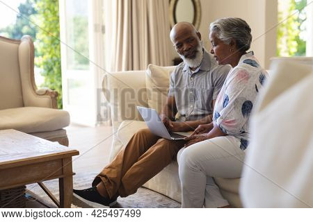 Senior african american couple sitting on sofa using laptop and talking. retreat, retirement and happy senior lifestyle concept.