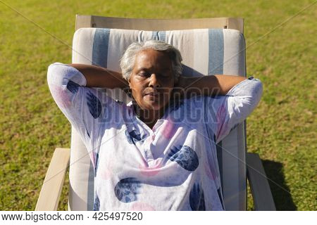 Senior african american woman relaxing in deckchair in sunny garden. retreat, retirement and happy senior lifestyle concept.