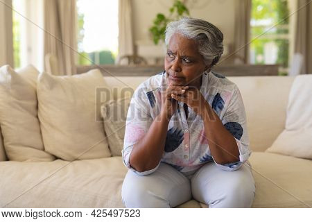 Senior african american woman sitting on sofa and thinking. retreat, retirement and senior lifestyle concept.