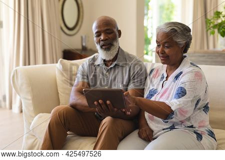 Senior african american couple sitting on sofa using tablet and smiling. retreat, retirement and happy senior lifestyle concept.