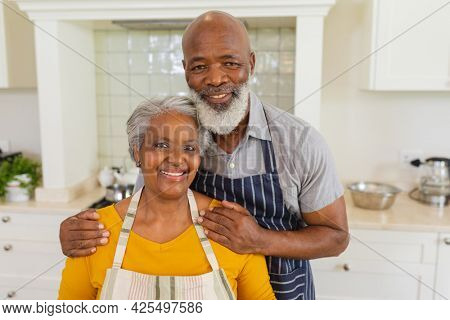 Portrait of senior african american couple in kitchen looking and camera and smiling. retreat, retirement and happy senior lifestyle concept.