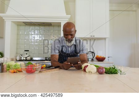 Senior african american man cooking in kitchen using tablet. retreat, retirement and happy senior lifestyle concept.