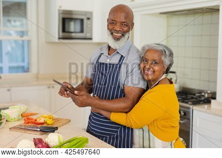 Portrait of senior african american couple cooking together in kitchen using tablet. retreat, retirement and happy senior lifestyle concept.
