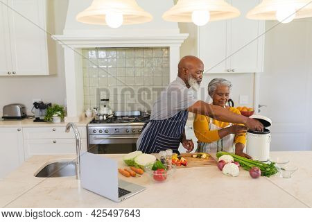 Senior african american couple cooking together in kitchen. retreat, retirement and happy senior lifestyle concept.