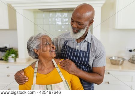 Senior african american couple in kitchen looking at each other and smiling. retreat, retirement and happy senior lifestyle concept.
