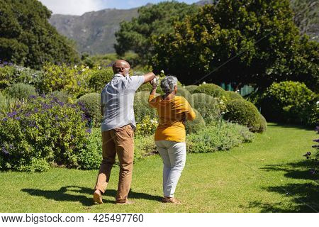 Senior african american couple spending time in sunny garden together dancing. retreat, retirement and happy senior lifestyle concept.