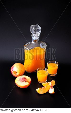 Homemade Apricot Liqueur In Two Glasses And A Glass Decanter, Next To Pieces Of Ripe Fruit On A Blac