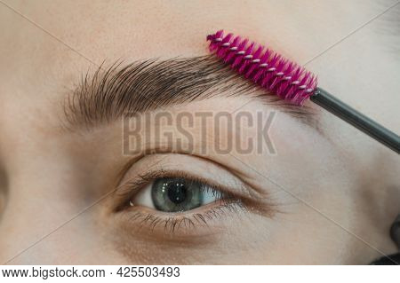 Combing, Plucking Eyebrows Close-up. Close Up Of Woman Doing Her Make Up, Preparing Brows Using Brus