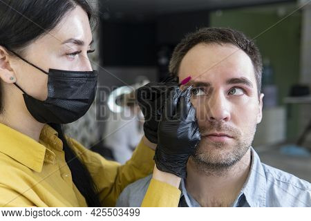 Young Man On The Procedure Of Eyebrow Correction In A Beauty Salon. Master Woman Removes An Eyelash