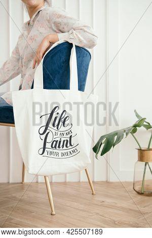 White tote bag mockup hanging on a blue velvet chair