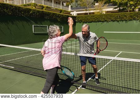 Senior caucasian couple playing tennis together on court highfiving. retirement retreat and active senior lifestyle concept.