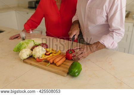 Mid section of senior caucasian couple cooking together in kitchen. retreat, retirement and happy senior lifestyle concept.