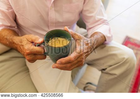 Mid section of senior caucasian man holding mug of coffee in living room. retreat, retirement and happy senior lifestyle concept.