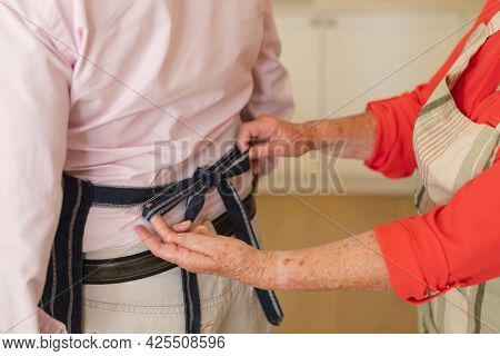 Mid section of senior caucasian couple tying apron in kitchen. retreat, retirement and happy senior lifestyle concept.