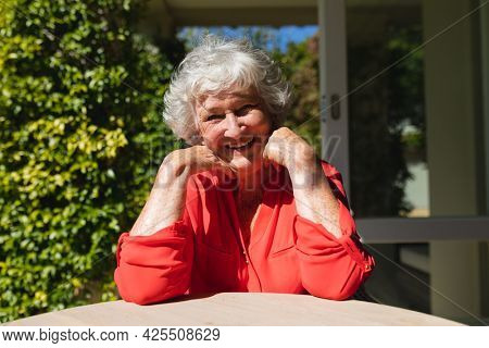 Portrait of senior caucasian woman sitting at table looking at camera and smiling in sunny garden. retreat, retirement and happy senior lifestyle concept.