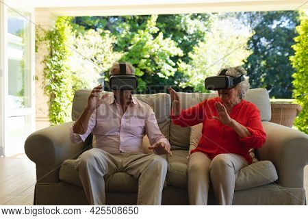 Senior caucasian couple sitting on sofa together wearing vr headset touching virtual screen. retreat, retirement and happy senior lifestyle concept.