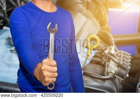 Auto Mechanic With Tool Working Check And Fixed An Old Car Engine At Service Station,change And Repa
