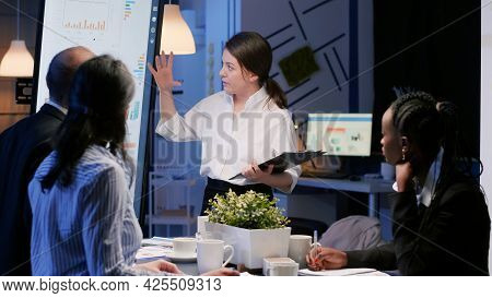 Focused Executive Manager Presenting Company Solution Using Presentation Monitor Working Overtime In
