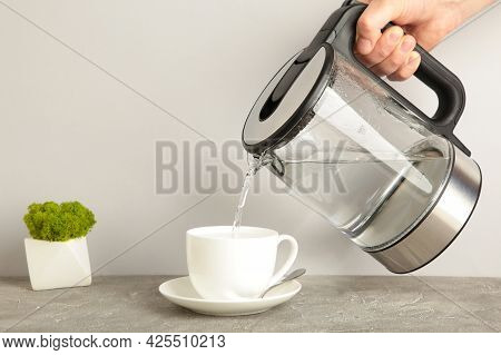 Kettle Pouring Boiling Water Into A Cup On Grey Background. Top View.