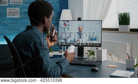 Internet Health Checkup Of Black Man Talking With Family Doctor Using Telehealth App While Sitting A