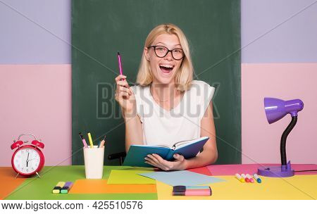 Female Teacher At Her Desk Marking Students Work. Pretty Teacher Smiling At Camera At The School. Un