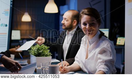 Portrait Of Smiling Businesswoman Looking Into Camera Working Overtime In Business Company Meeting O