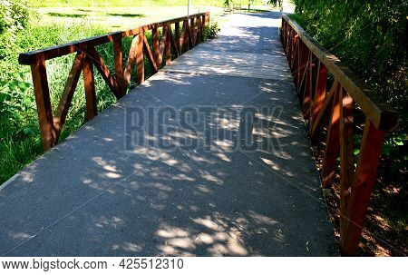 Wooden Bridge With A Stone Foundation Newly Built For Cyclists Over A Stream By The Pond. Wooden Bea