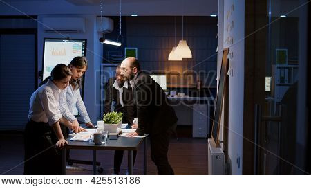 Multi Ethnic Businesspeople Lean On Conference Table Analyzing Company Strategy Ideas Overworking At