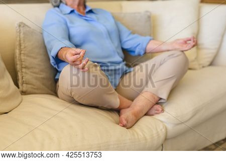 Mid section of senior caucasian woman sitting on sofa meditating. retreat, retirement and happy senior lifestyle concept.