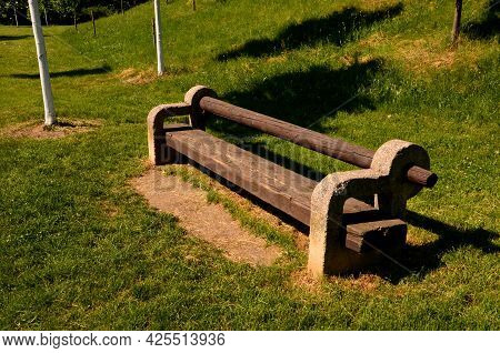 In The Park. Solid Concrete Bench With A Log As A Backrest. Perennial Flower Beds And Lawns In The B