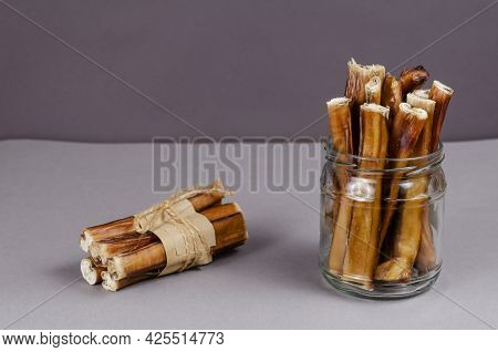 Pet Treats In A Glass Jar On A Gray Background. Dried Bully Sticks For Dogs. Beef Pizzle. Air-dried