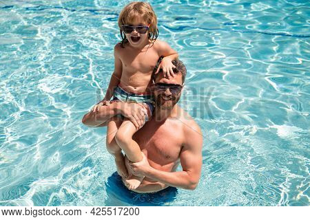 Father And Son Swimming In Pool, Summer Family. Child With Dad Playing In Swimming Pool. Family In P