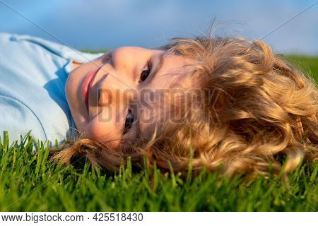 Carefree Child Laying On Green Summer Meadow In The Summer On Nature. Happy Kid Fun With Cheerful Sm