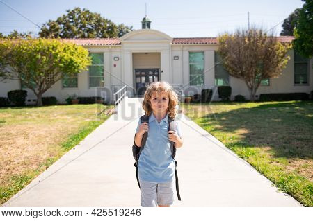 Portrait Of Child Pupul With Rucksacks In The Park Near School. Schoolboy With Backpacks Outdoors. S