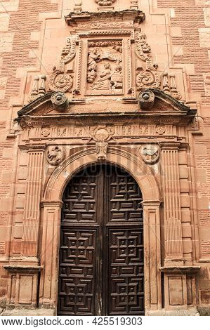 Old Stone Facade Made Of Carved Stone And Vintage Wooden Door In A Majestic House In Villanueva De L