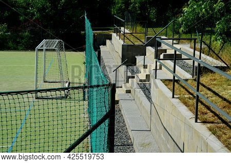 Outdoor Playground For Ball Games. High Barriers Fencing Protect Spectators On A Concrete Tribune In