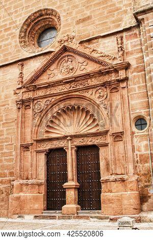 Old Stone Facade Made Of Carved Stone And Vintage Wooden Door In Encarnación Church In Villanueva De