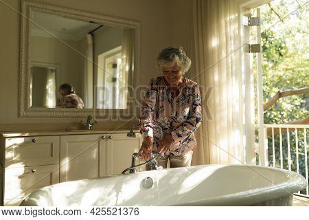 Senior caucasian woman running a bath in bathroom. retreat, retirement and happy senior lifestyle concept.