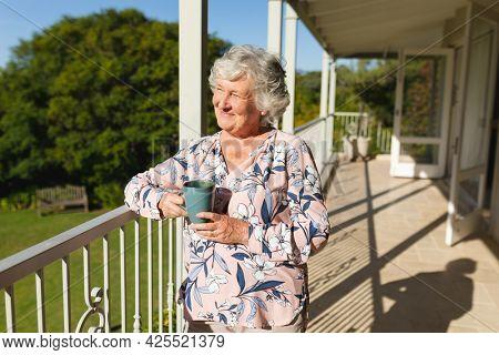 Senior caucasian woman standing on balcony holding mug and smiling. retreat, retirement and happy senior lifestyle concept.
