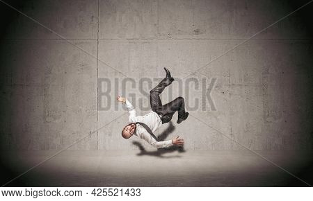 businessman falling on concrete background.