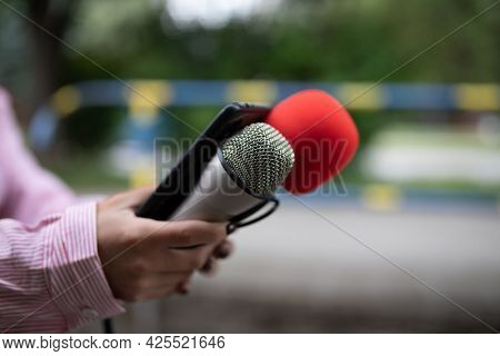 Professional woman journalist at event, holding microphones and recording notes on smartphone dictaphone