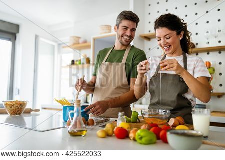 Happy Young Couple Preparing Food In Kitchen At Home