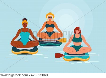 Group Of Young Women In Swimsuits Sit In Lotus Position On A Stand Up Paddle Board In The Sea. Paddl