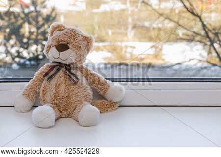 A Small Plush Toy Kitten With A Bow Sits On A White Windowsill. Soft Toy, Gift